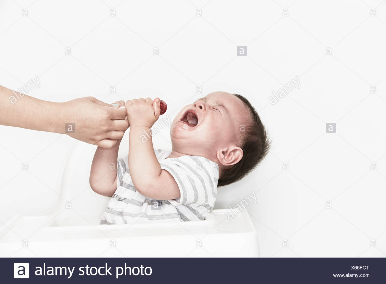 Hand taking lollipop from crying baby - Stock Image