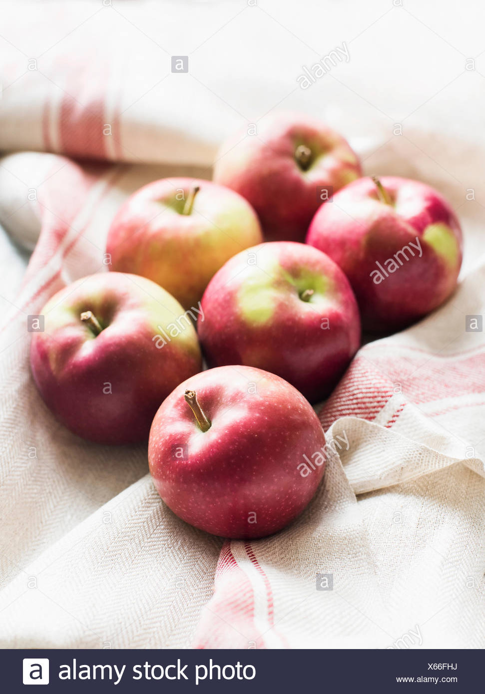 Six red apples on linen kitchen cloth, close-up - Stock Image