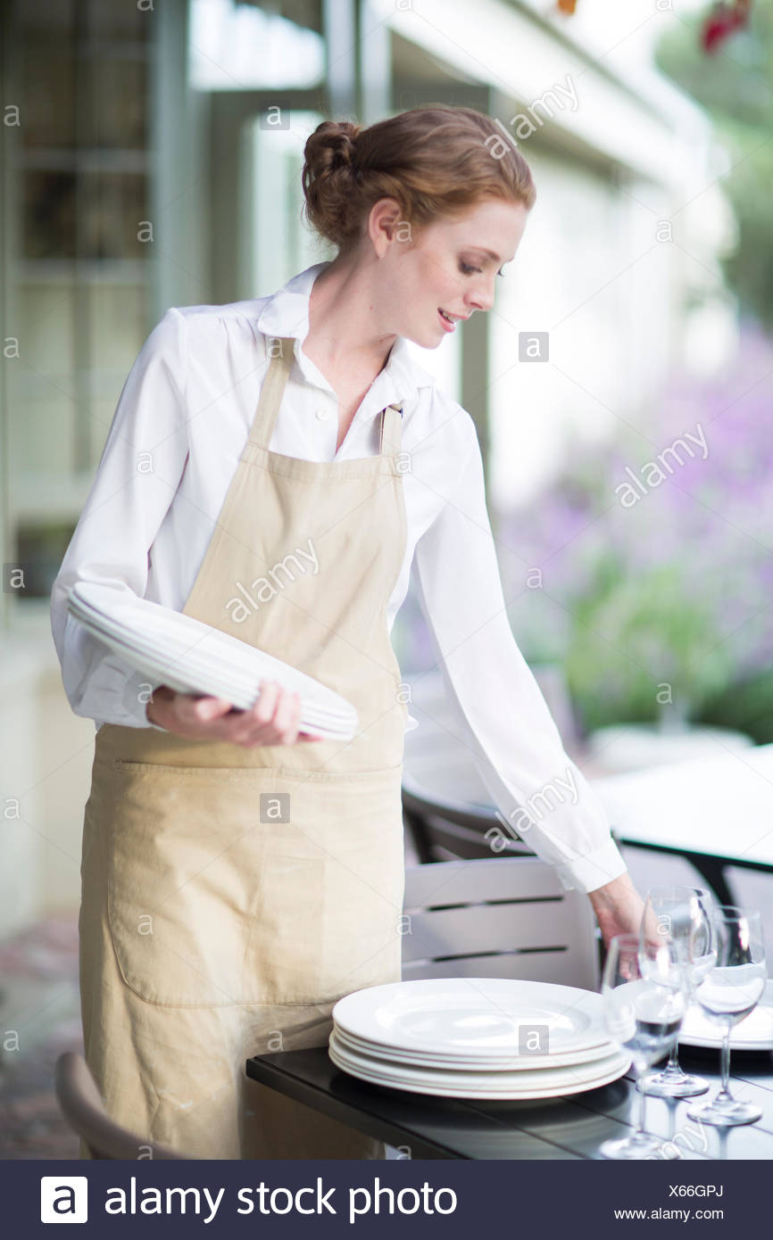 Waitress organizing plates on table in patio restaurant - Stock Image