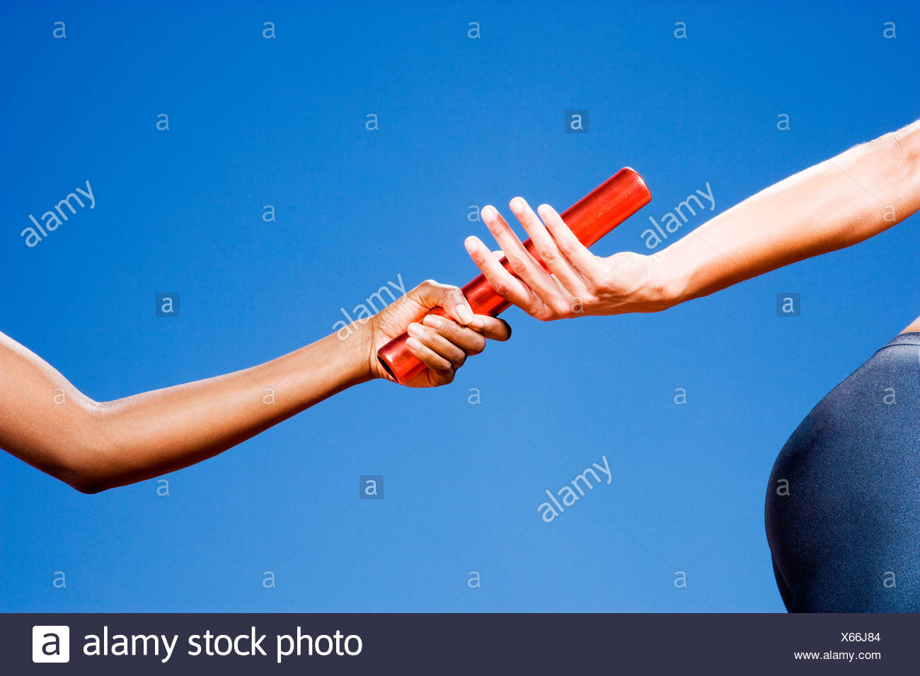 Baton passing between relay runners - Stock Image