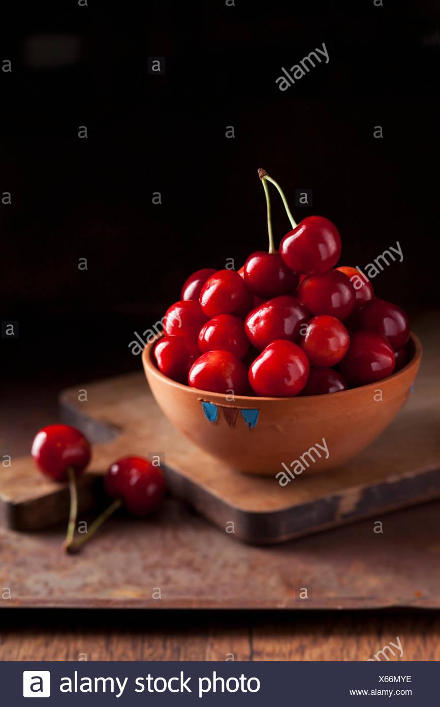 Fresh ripe cherries in a bowl on dark background - Stock Image