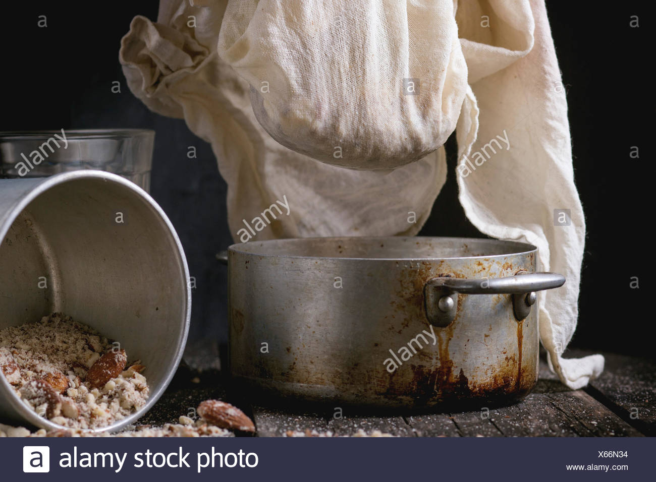 Process of making non-dairy almond milk - extraction of grain almond via white textile at vintage pan over old wooden table. Dar - Stock Image