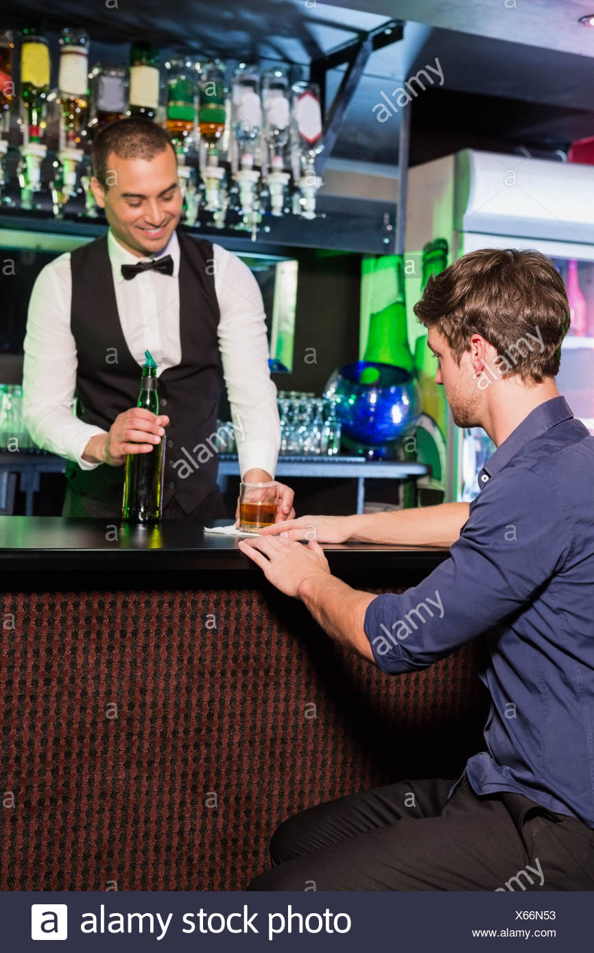 Bartender serving whiskey to man Stock Photo: 279202143 - Alamy