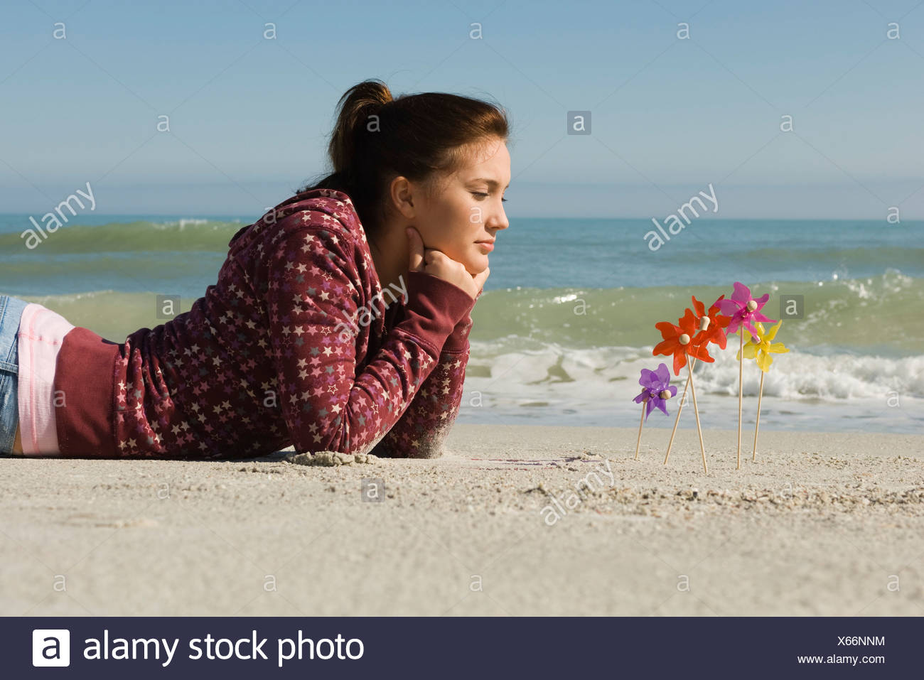 Preteen Girl Lying On Stomach On Beach Contemplatively