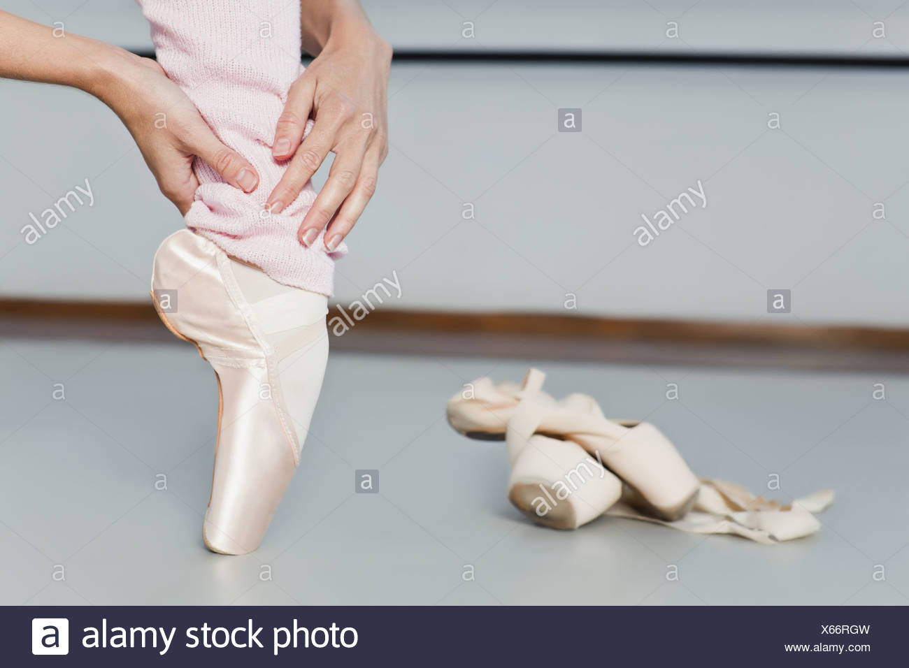 Ballet dancer examining toes on pointe - Stock Image