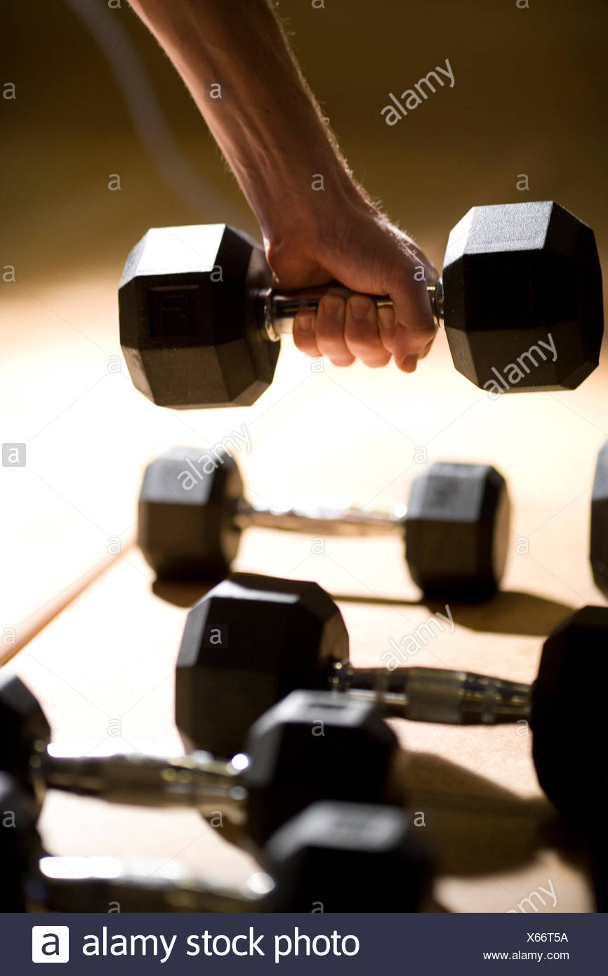 A hand grabs for a free weight on the floor of a personalized workout studio - Stock Image