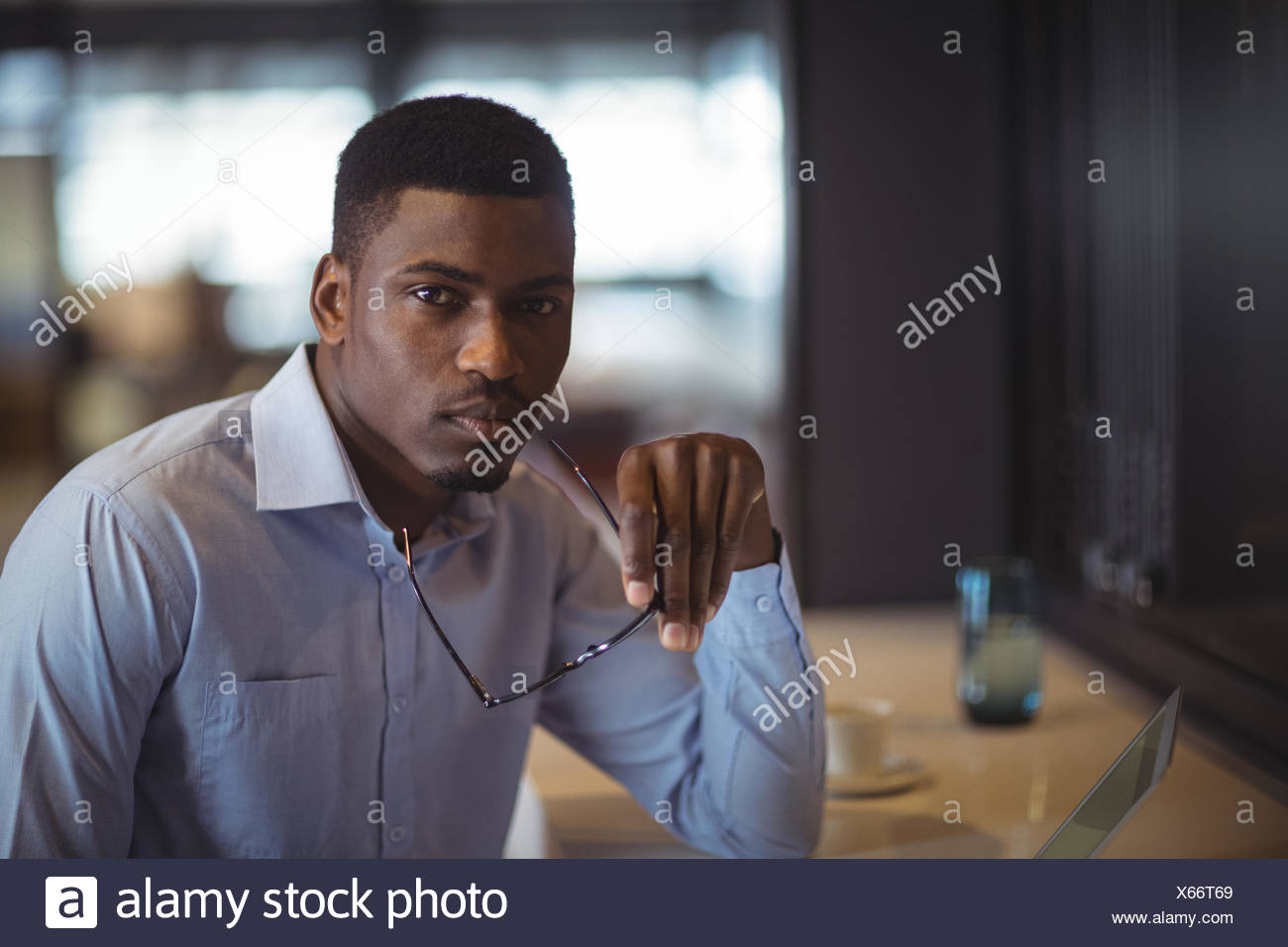 Businessman holding spectacle sitting at desk - Stock Image