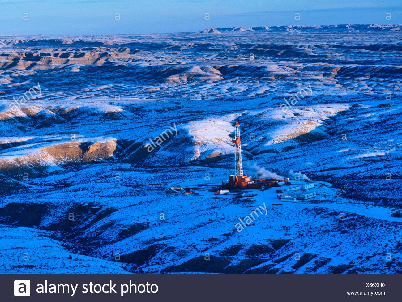 Onshore Oil Drilling Rig in Mountainous Snow Covered Terrain - Stock Image