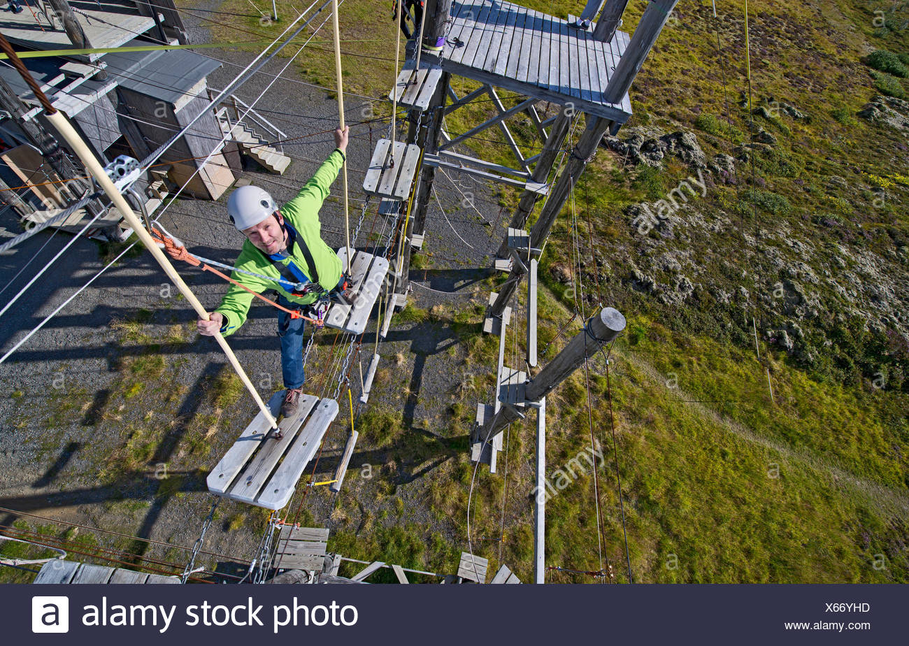 Mature man walking on wooden planks on high rope course - Stock Image