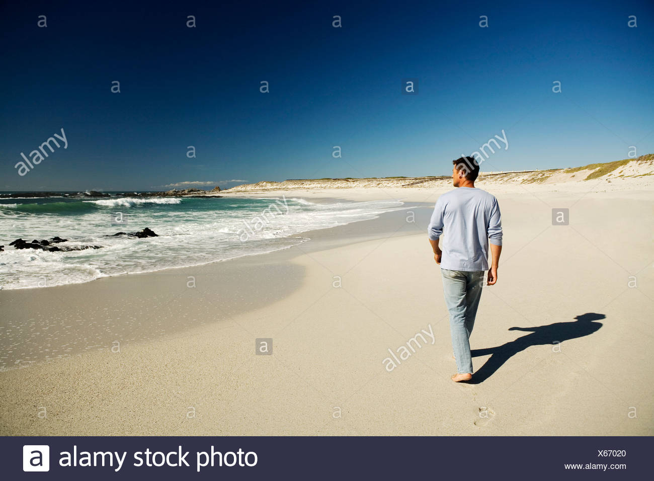 Ma walking on the beach rear view - Stock Image