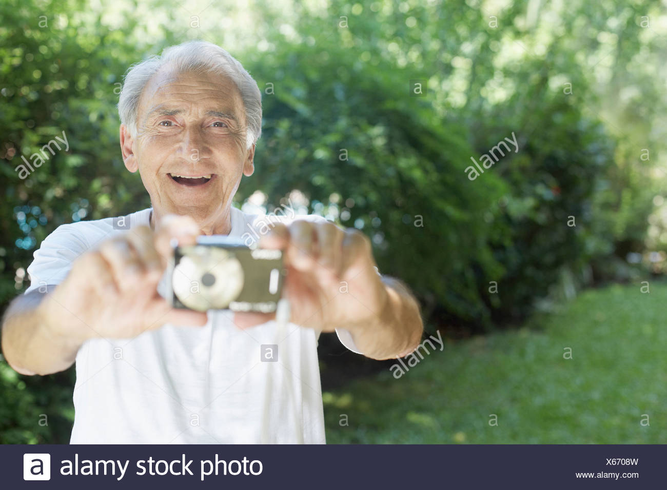 Senior man outdoors holding out digital camera and smiling - Stock Image