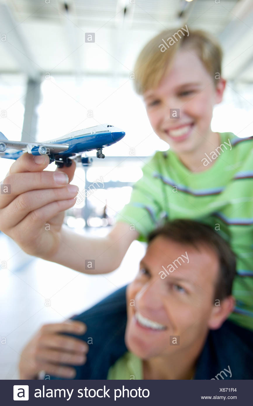 Father carrying son  on shoulders in airport, boy holding toy aeroplane, smiling differential focus Stock Photo
