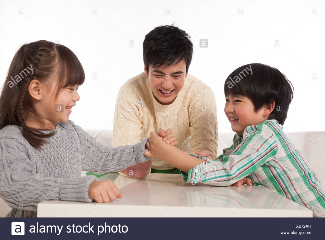 Boys and girls in an arm-wrestling father do referees - Stock Image