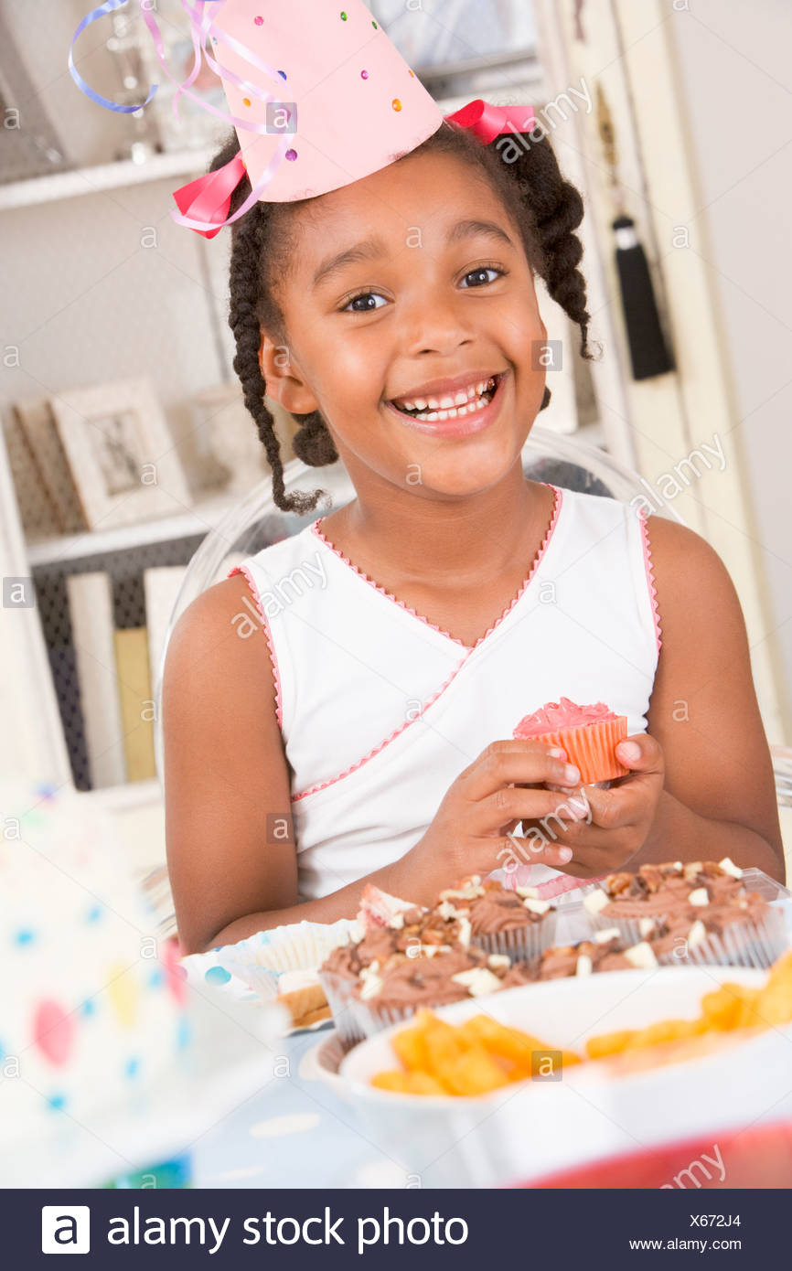 Young girl at party sitting at table with a cupcake smiling - Stock Image