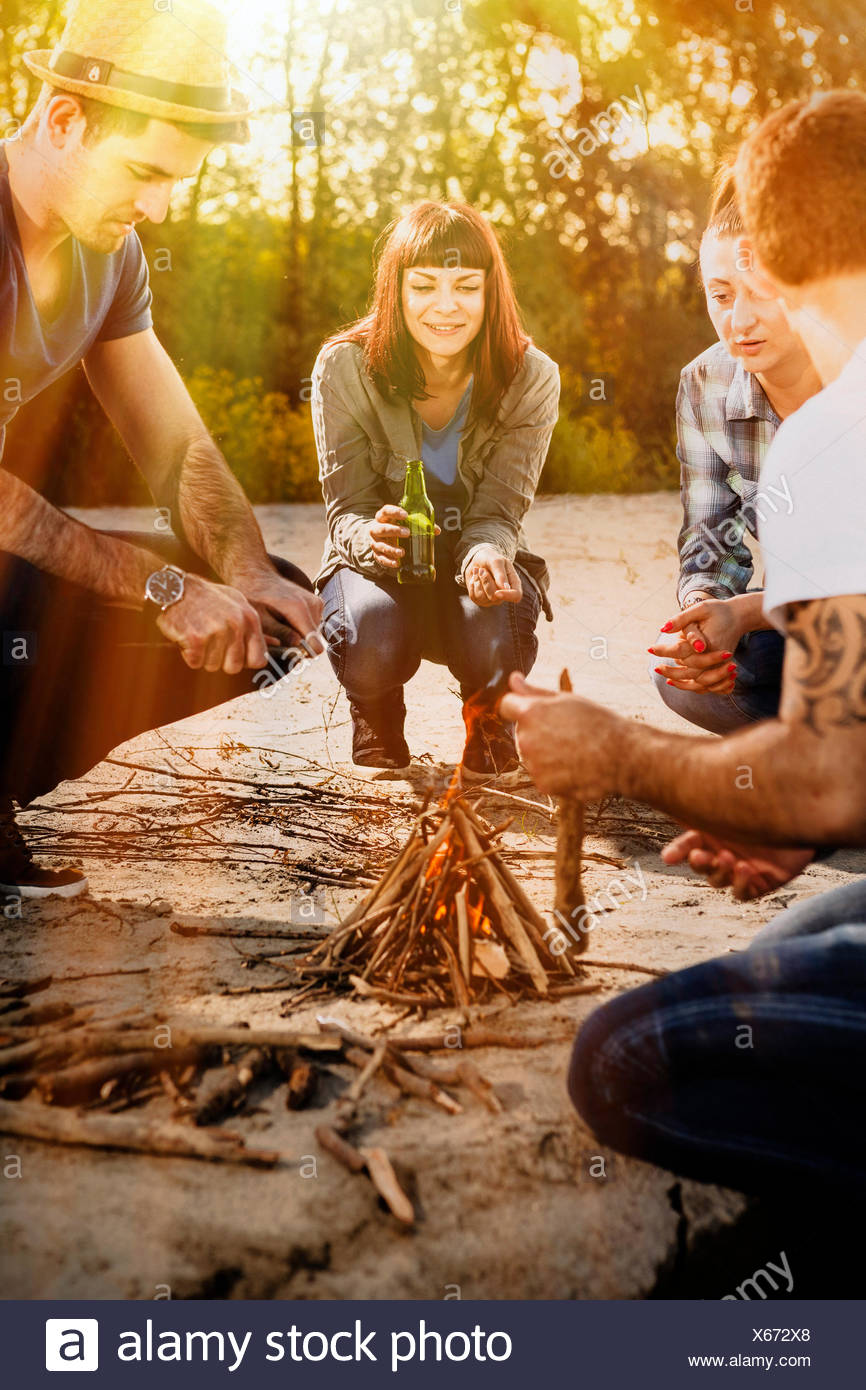 Group of friends lighting campfire on a riverbank, Osijek, Croatia - Stock Image
