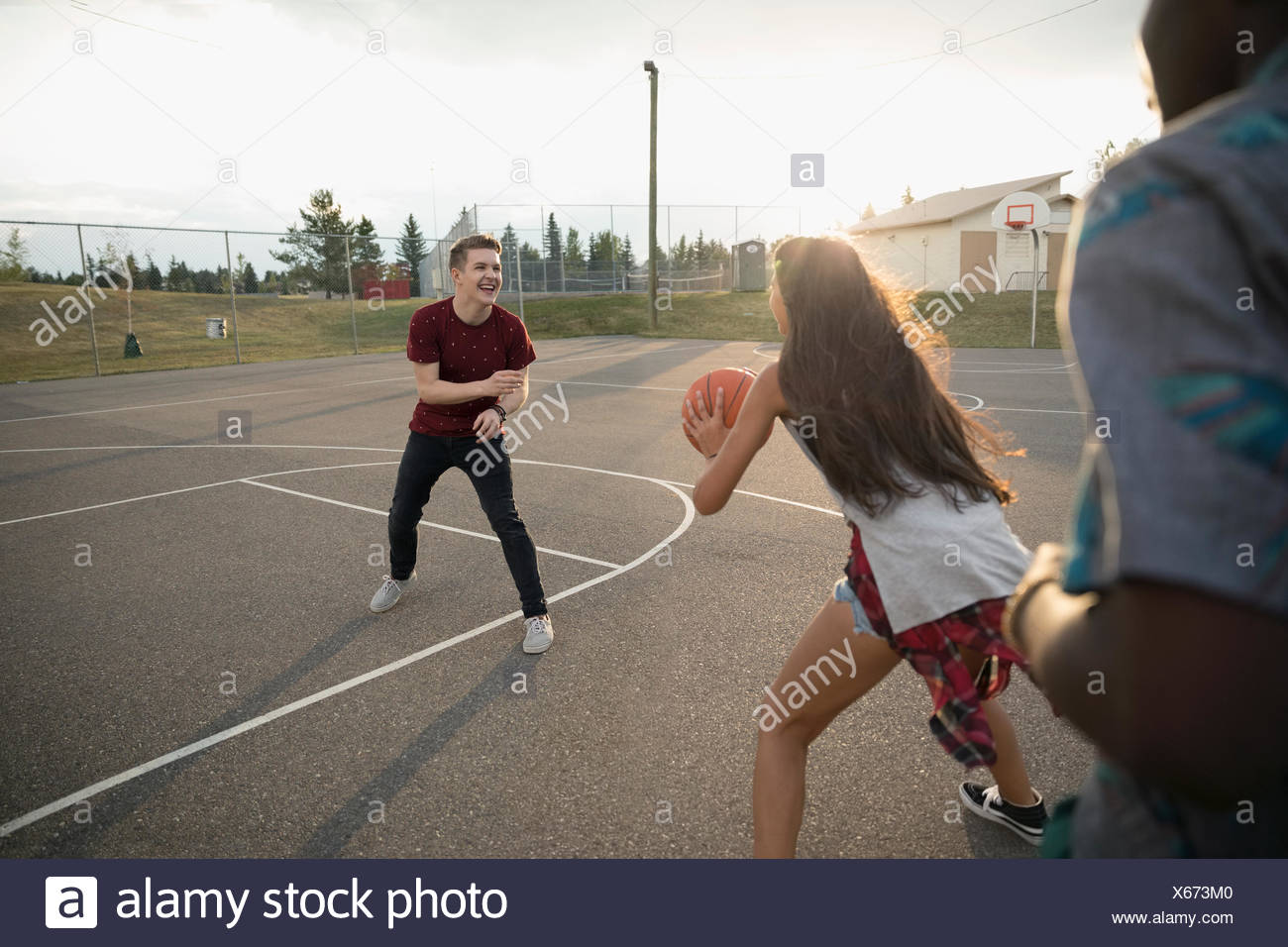 Teenage friends playing basketball on outdoor basketball court Stock Photo