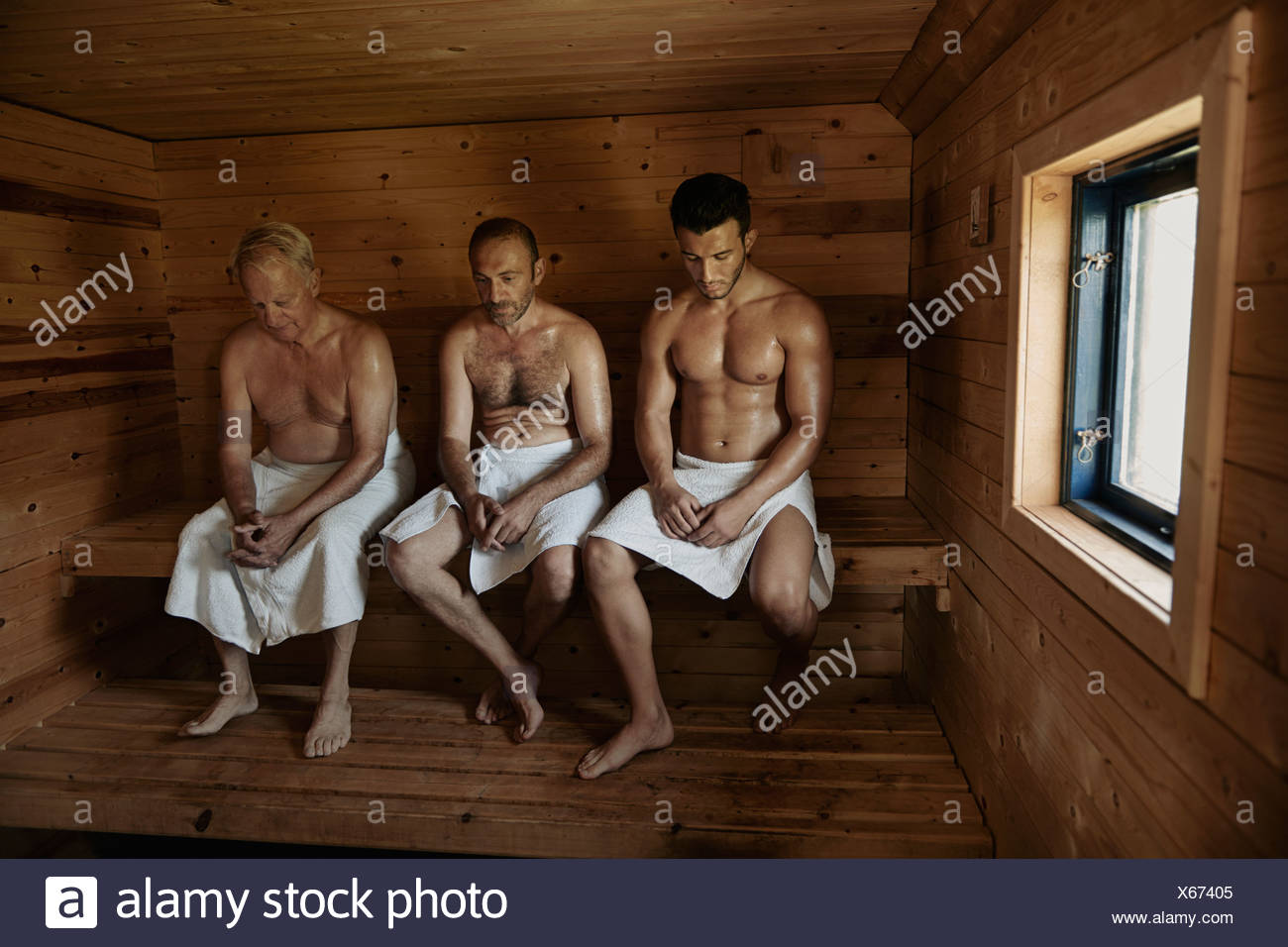 Three men sitting in sauna with heads bowed - Stock Image