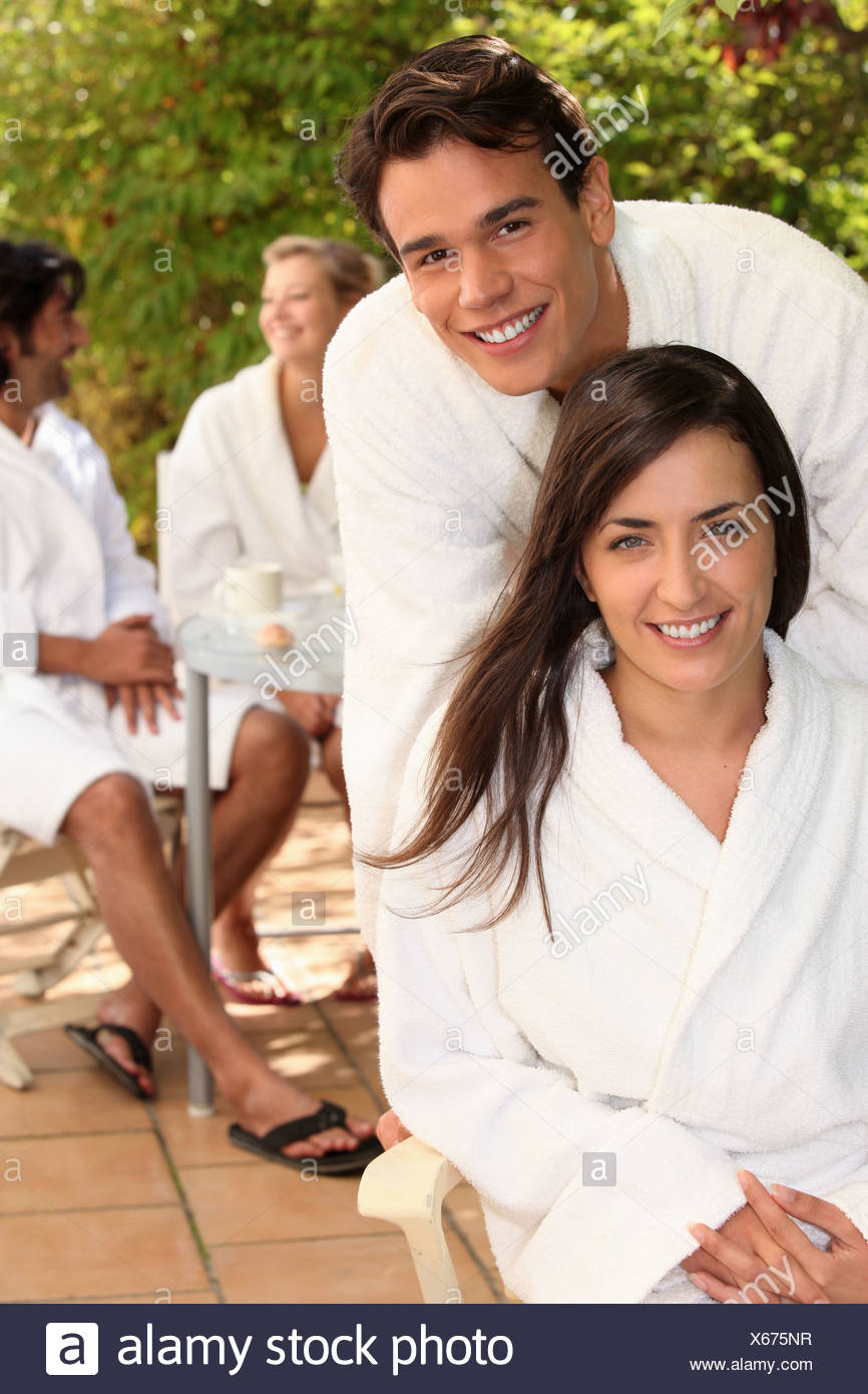 Couple with friends sitting on a terrace in toweling robes Stock Photo