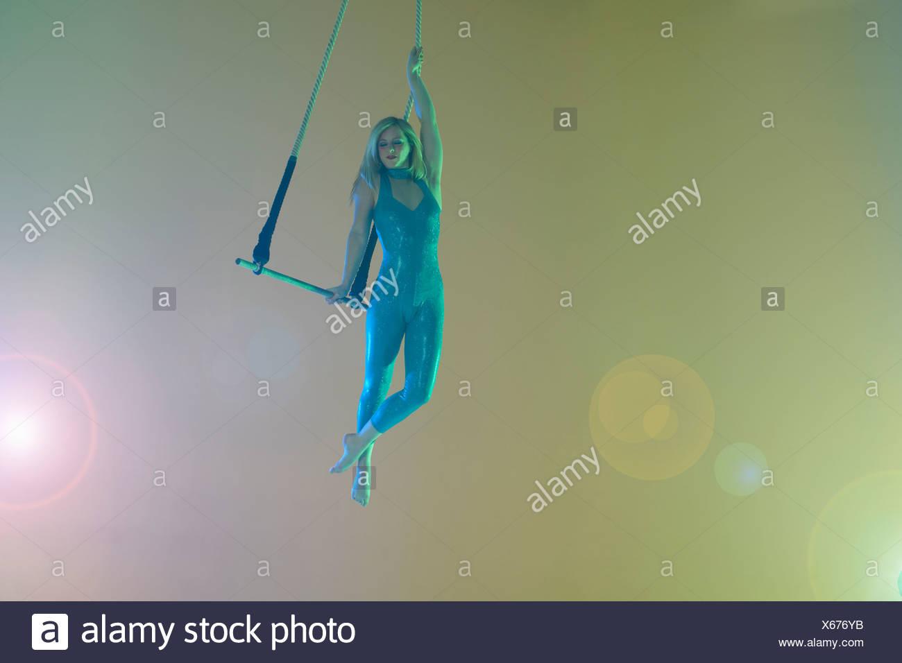Trapeze artist holding trapeze Stock Photo