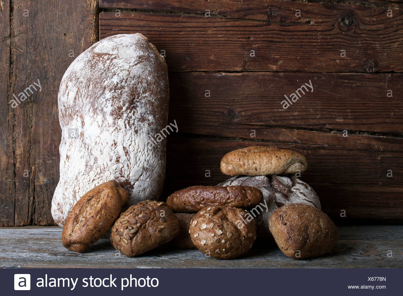 Loaf of Bread and rolls on a rustic wooden surface Stock Photo