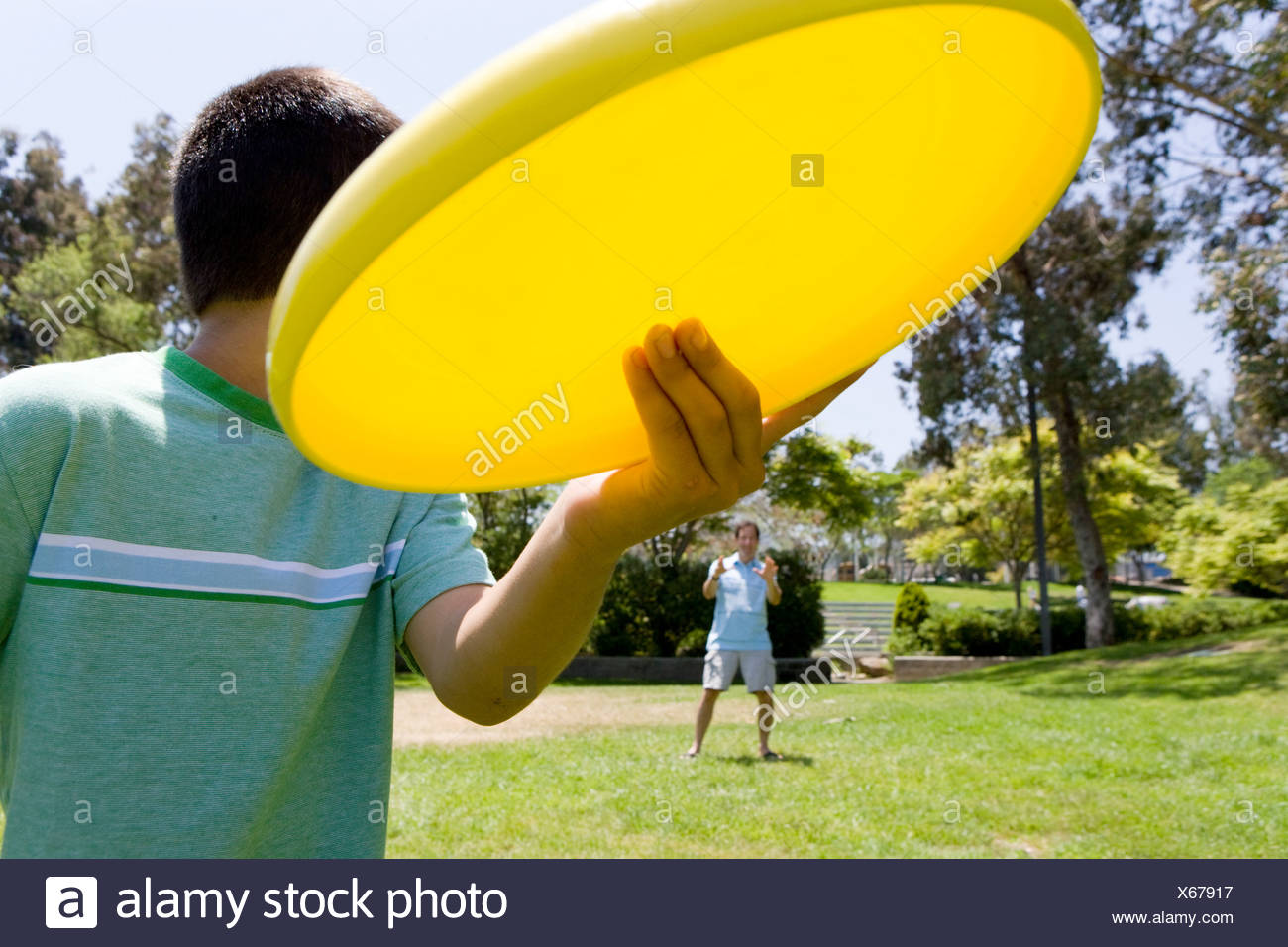 Boy (8-10) playing with plastic disc - Stock Image