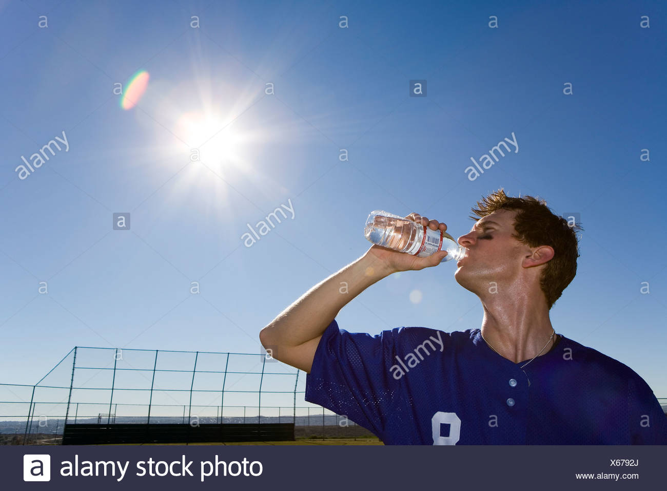 Sportsman drinking water from bottle on pitch, profile, low angle view lens flare - Stock Image