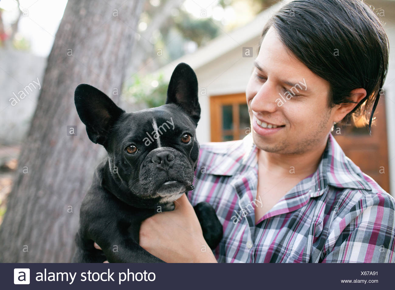 Portrait of young man carrying dog - Stock Image