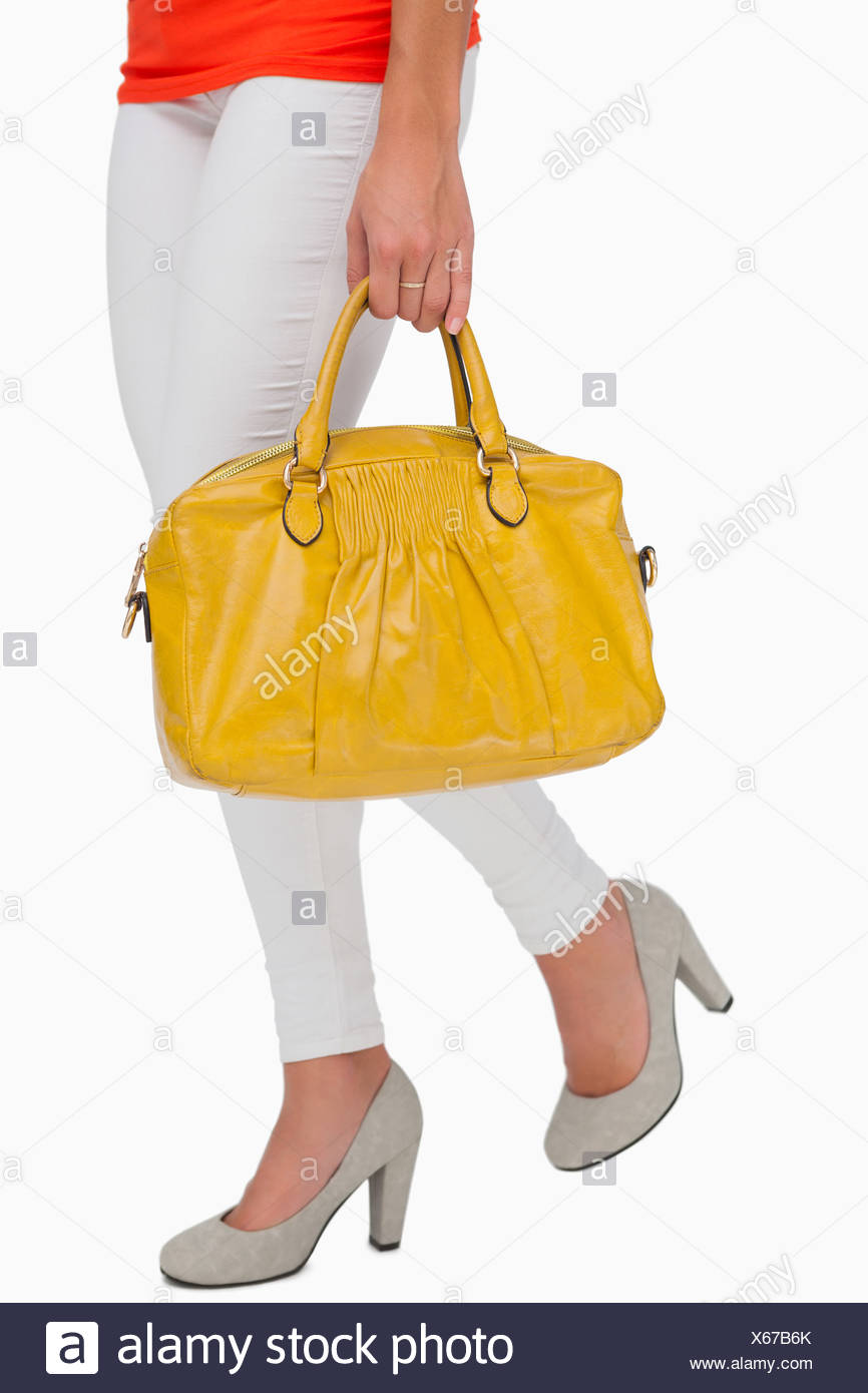 Woman in high heels walking with yellow bag - Stock Image