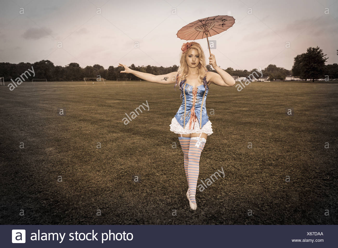 A woman wearing a laced basque, stockings and suspenders, holding an umbrella A carnival circus outfit - Stock Image
