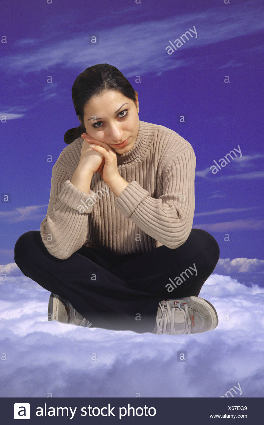 young woman sitting on a cloud - Stock Image