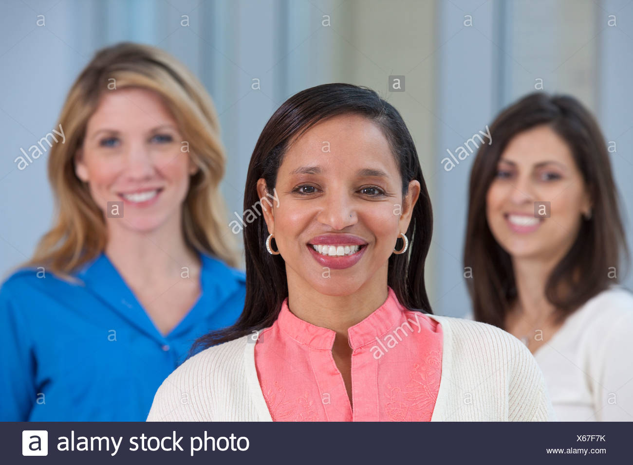 Portrait of a Hispanic woman smiling with her friends in the background Stock Photo