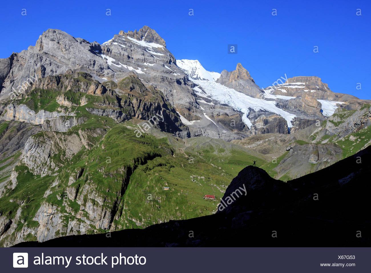 Hiker admires Lake  Oeschinensee Bernese Oberland Kandersteg Canton of Bern Switzerland Europe - Stock Image