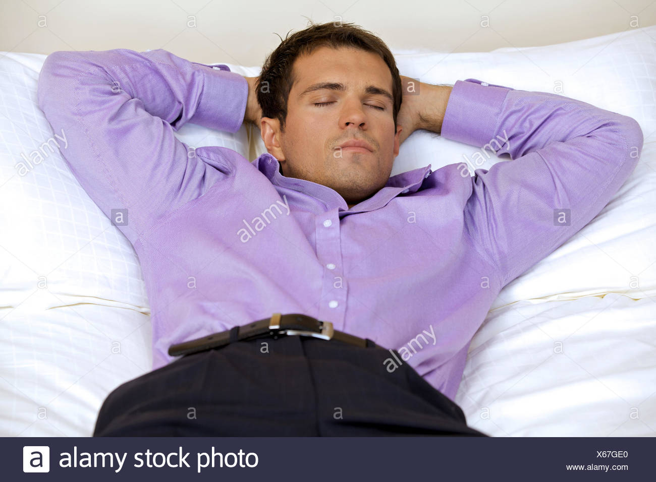 Man relaxing in hotel room with hands behind head, eyes closed - Stock Image