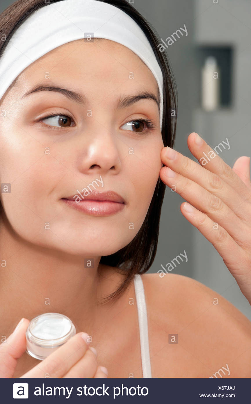 Woman applying moisturizer in mirror - Stock Image