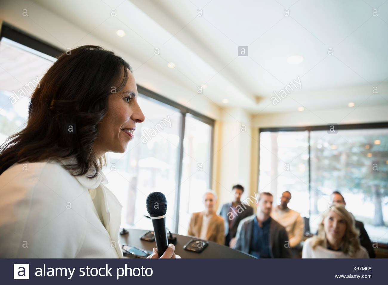 Businesswoman with microphone leading conference - Stock Image