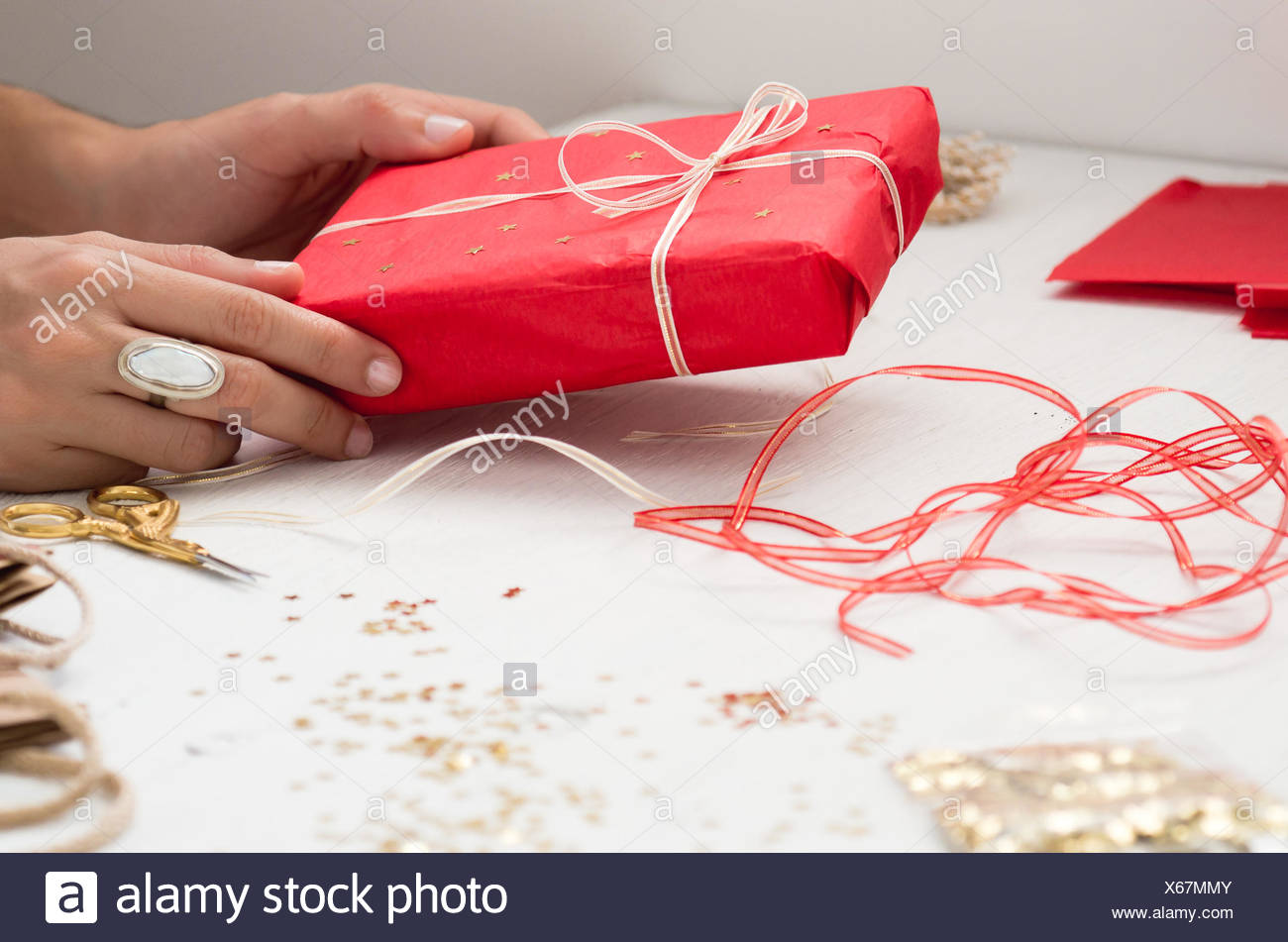 Cropped Image Of Hand Holding Gift Box On Table Stock Photo