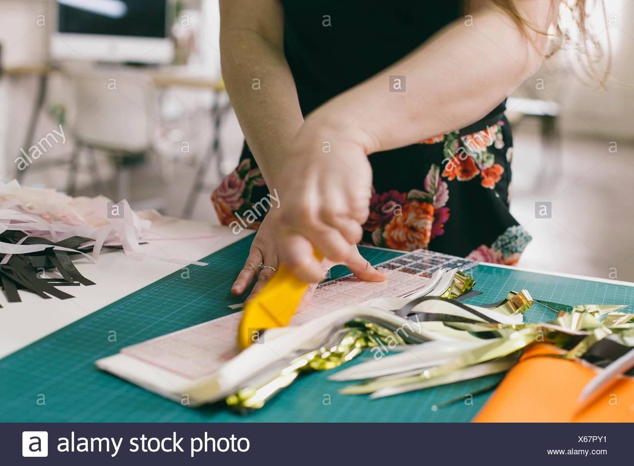 Close up of female textile designer cutting textiles in design studio - Stock Image