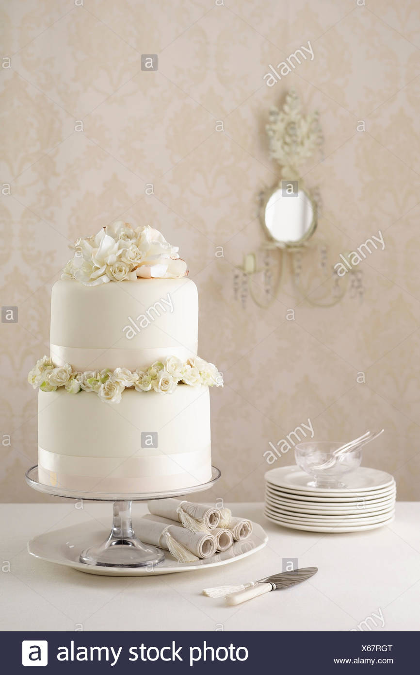 Two tier wedding cake with knife and plates Stock Photo: 279225992 ...