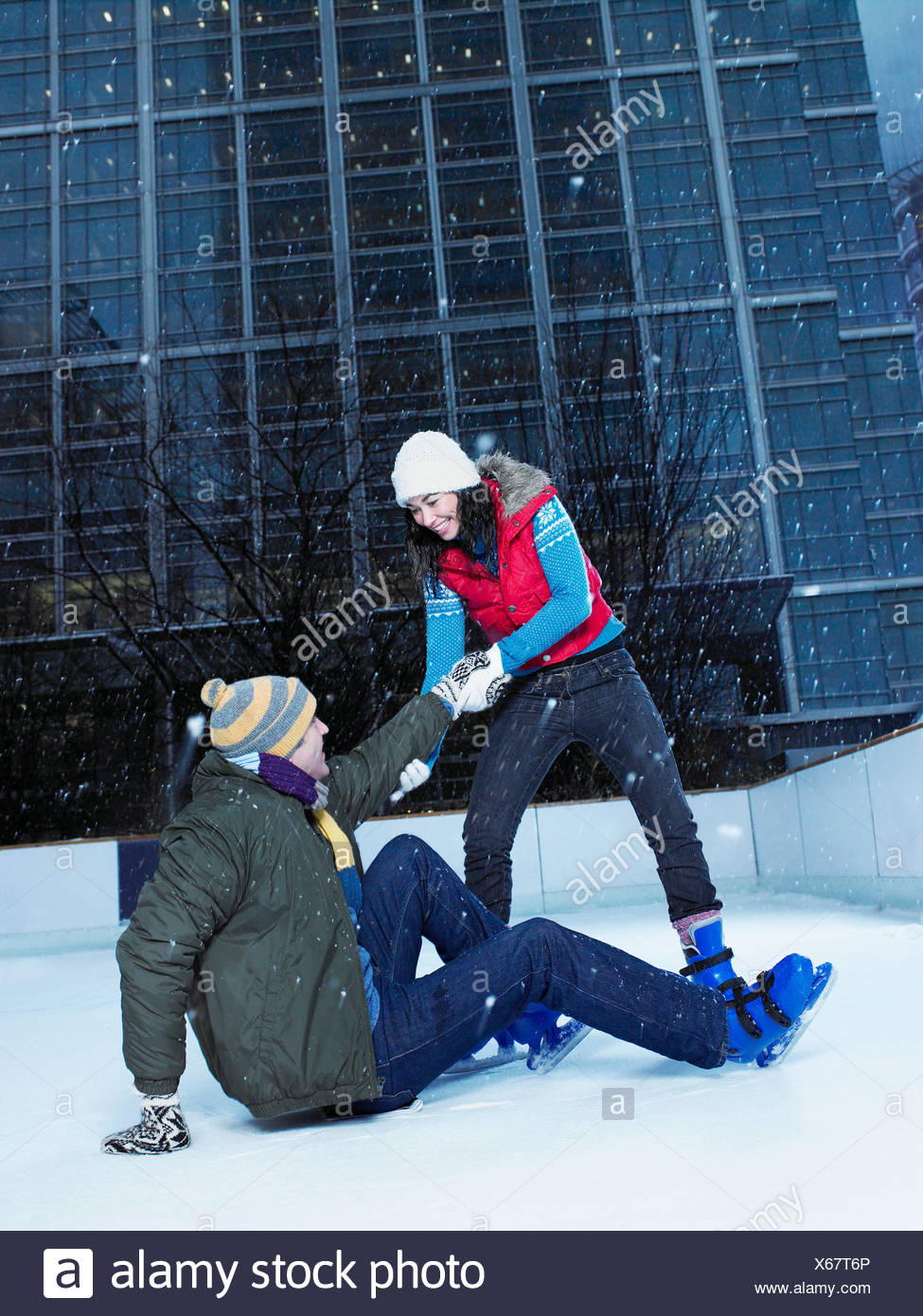 Woman helping man up from ice rink - Stock Image