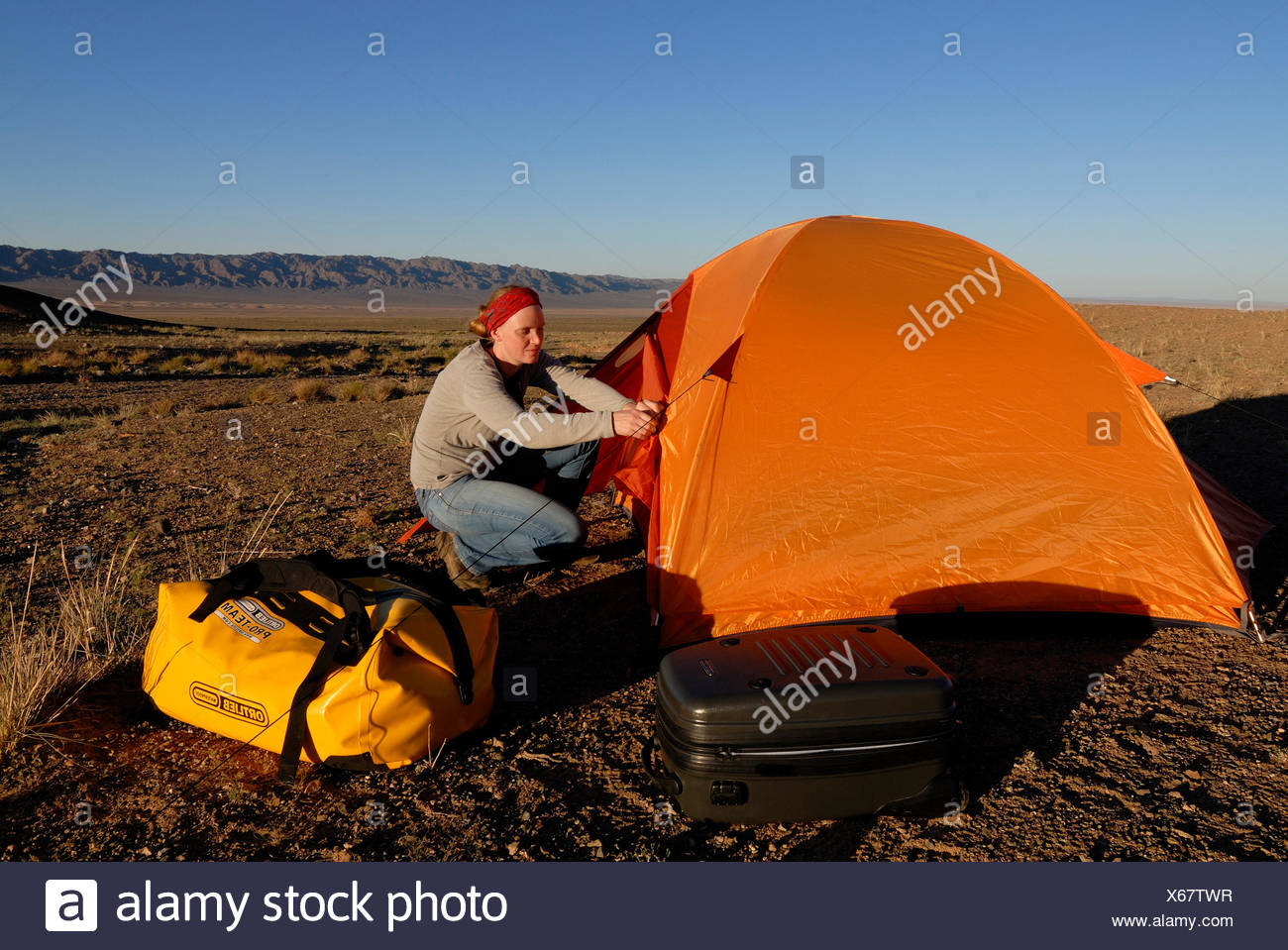 542fd860b56692 Young woman setting up camp with orange trekking tent and outdoor equipment  in the Gobi Desert