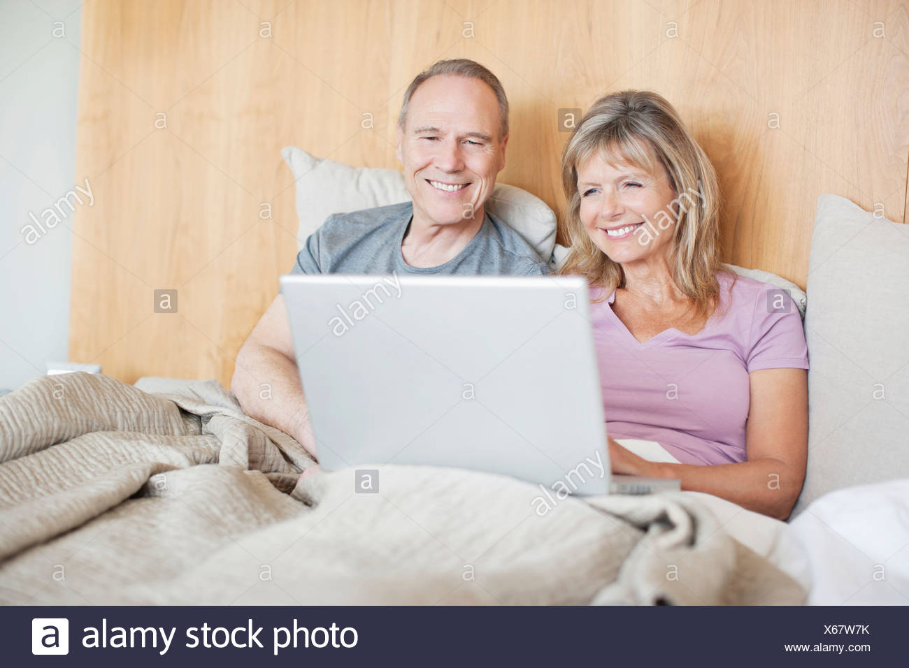 Couple sitting in bed using laptop together - Stock Image
