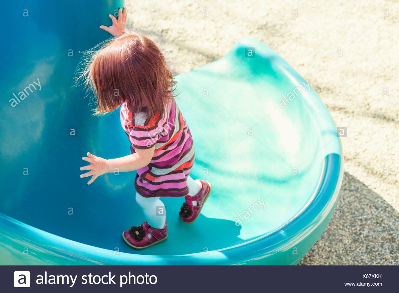 Baby girl climbing slide at playground - Stock Image