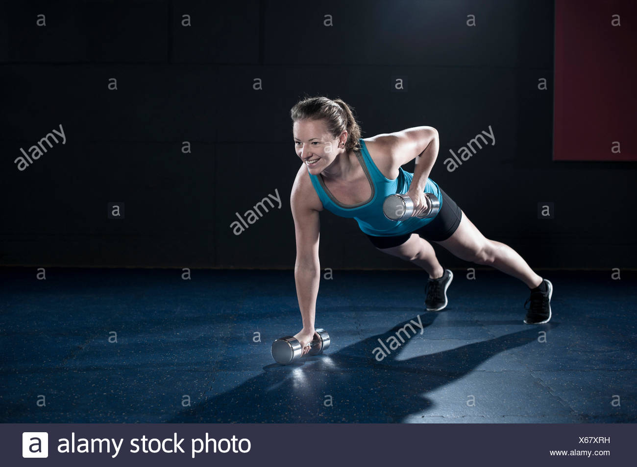 Sportive young woman doing exercise with dumbbell in the gym, Bavaria, Germany - Stock Image