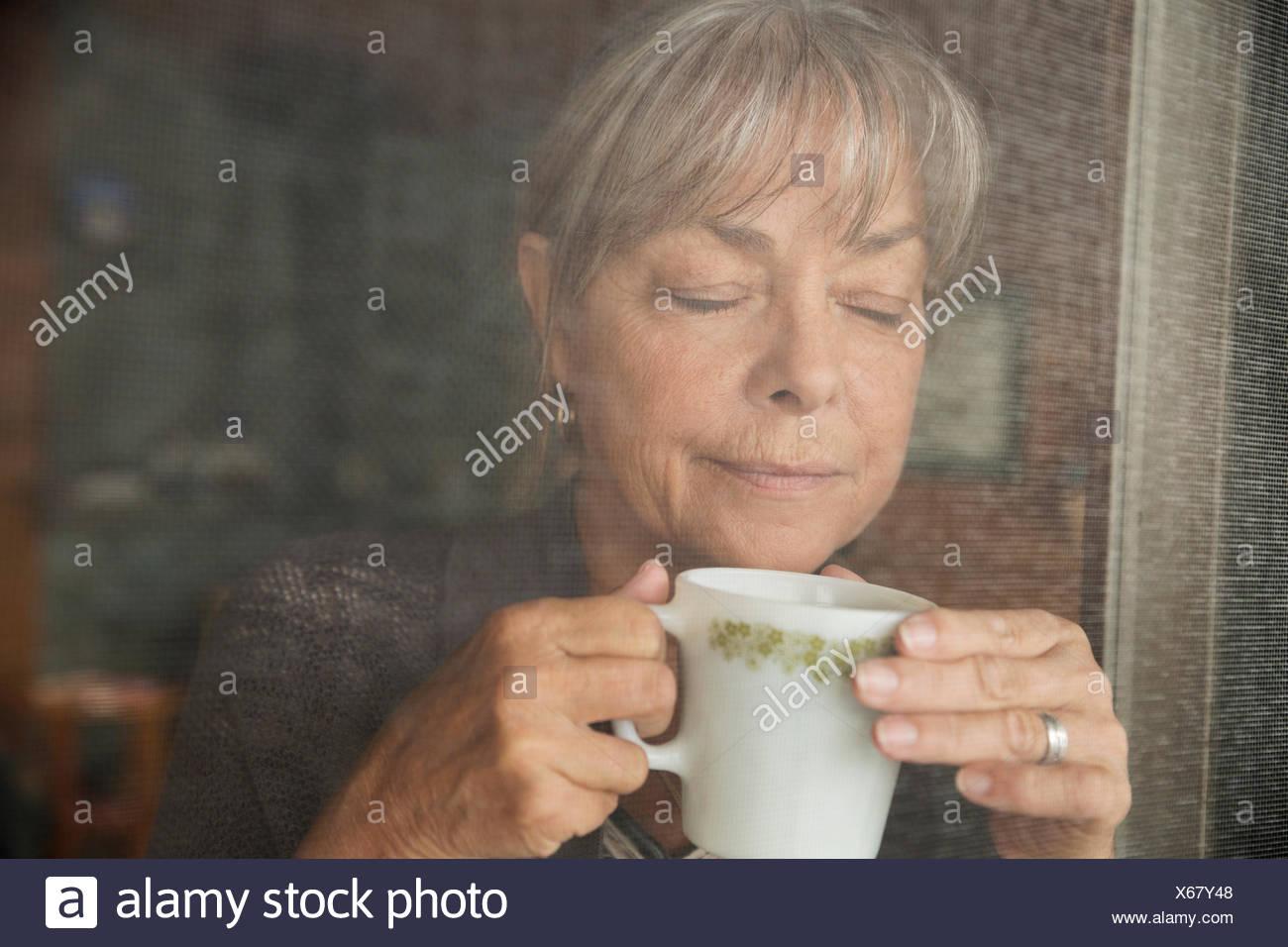 Close up serene woman drinking coffee screen door - Stock Image