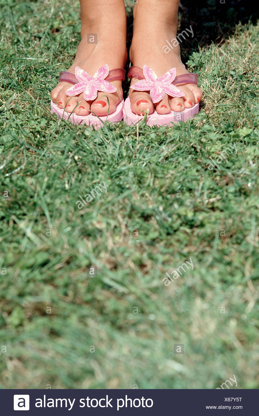85b0a63c2b518 Cropped female ankles and feet wearing pink flip flops with sequined flower  and red nail polish