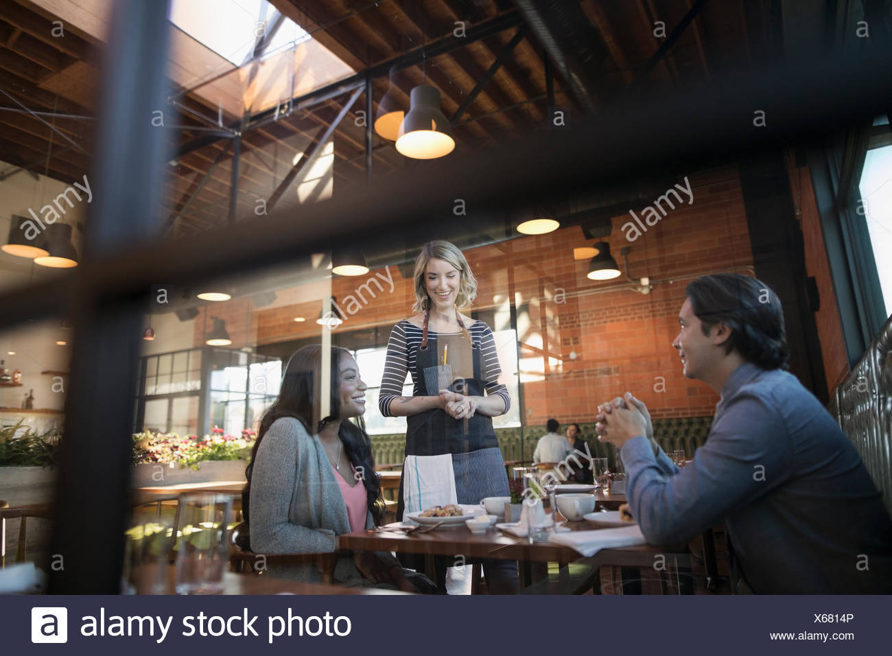 Female server serving food to couple at restaurant table - Stock Image