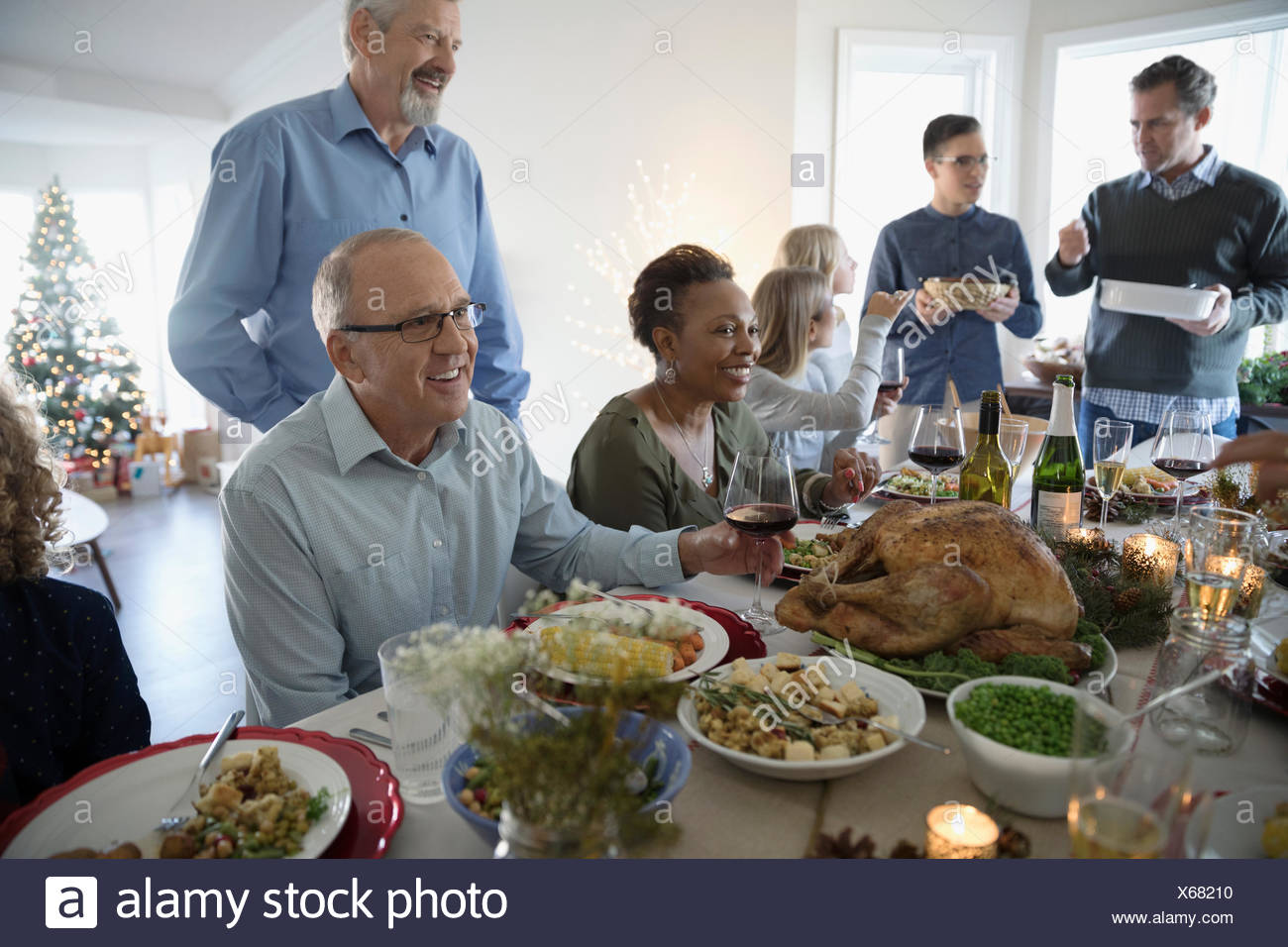 Family enjoying turkey Christmas dinner at table - Stock Image