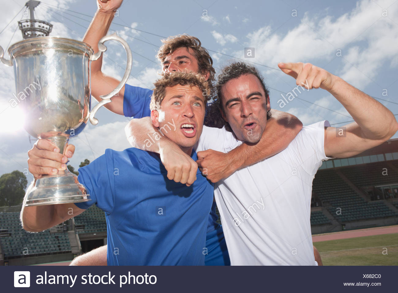 Soccer players cheering with trophy - Stock Image