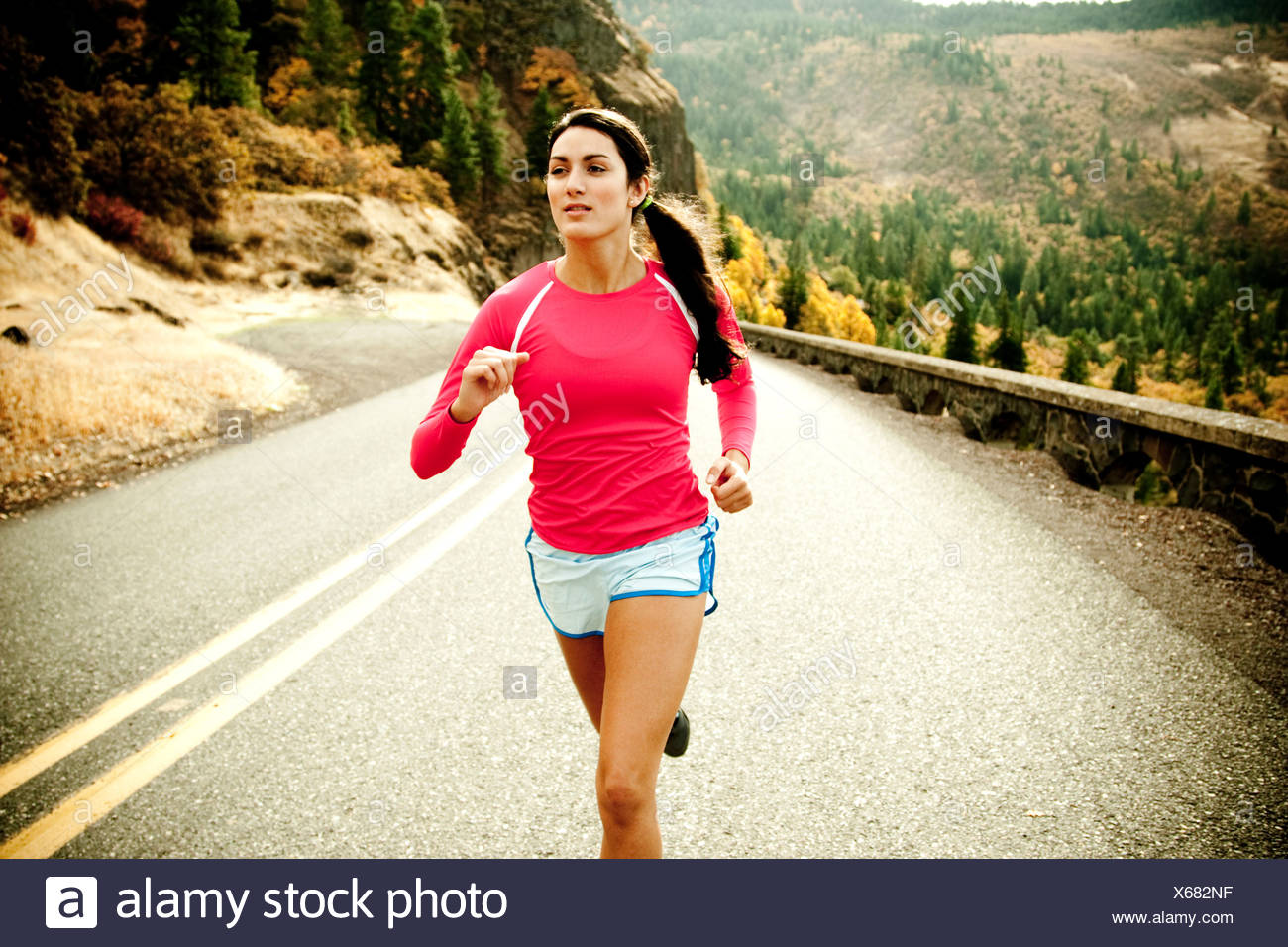 An athletic woman jogging along a deserted road on a beautiful fall day. - Stock Image