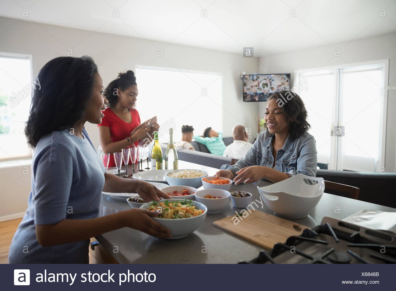 African American mother and teenage daughters cooking in kitchen - Stock Image